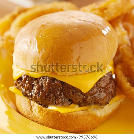 miniburger closeup with melted cheese and onion rings. - stock photo