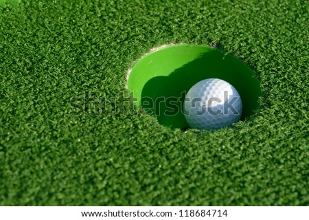 Minigolf ball in a hole closeup - stock photo