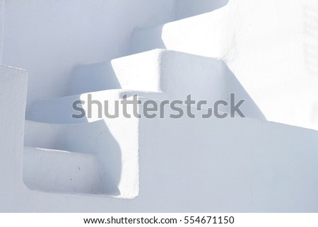 Minimal white stone staircase between two white walls, Oia, Santorini, Greece.