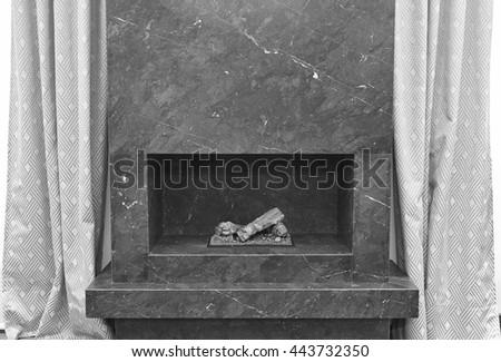 Minimalism stone fireplace. Apartment interior detail. Black white - stock photo