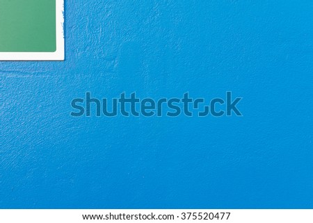 Minimalism style, Blue wall texture background with green label and white border on the top angle.