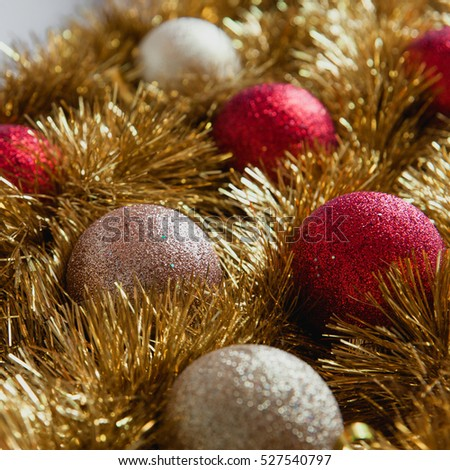 Minimalist Christmas decorations in two colors: red and gold balls with shiny yellow tinsel. New year background.
