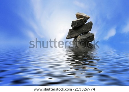 minimalist conceptual stacking stones in the middle of ocean. digital compositing with colour tone, water reflection and ripple effects. - stock photo