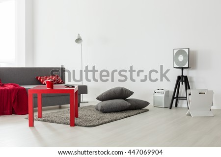 Minimalist interior of a bright living room with a grey sofa, red coffee table and a pile of cushions - stock photo