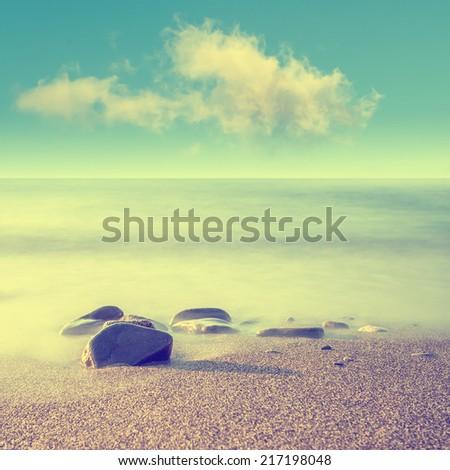 Minimalist misty seascape with rocks at long exposure. Coastal Sunrise. - stock photo