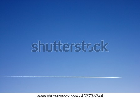 Minimalist photo of airplane contrail in blue sky - stock photo