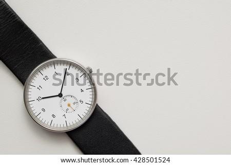 Minimalist wristwatch white dial on white background - stock photo