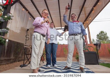 Minister with male gay couple celebrating their marriage - stock photo