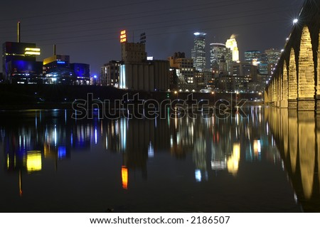 Minneapolis at night reflected in the river with the Stone Arch Bridge