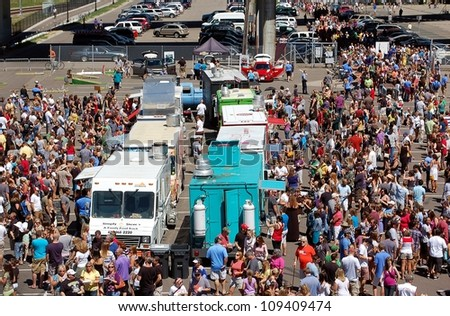 MINNEAPOLIS - AUGUST 5:  A large crowd attends the MN. Food Truck Fair on August. 5, 2012, in Minneapolis.  Food Trucks have become popular by providing good food at reasonable prices.  prices. - stock photo