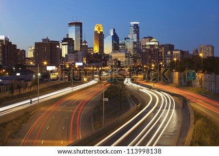 Minneapolis. Image of Minneapolis skyline and highway with traffic lines leading to the city. - stock photo