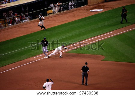 MINNEAPOLIS - JULY 17:  Michael Cuddyer stretches to catch the ball, A.J. Pierzynski runs to first and Orlando Hudson makes the correct call of out at Target Field July 17, 2010 in Minneapolis, MN - stock photo