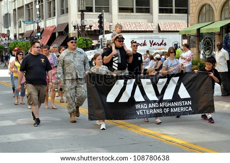 MINNEAPOLIS - JULY 28:  Veterans march in the Twin Cities Heroes Parade on July 28, 2012, in Minneapolis.  The parade honors post-9/11 veterans and active duty military. - stock photo
