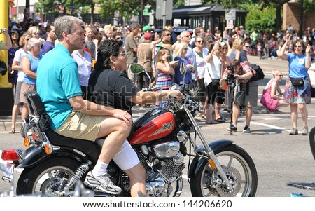 MINNEAPOLIS - JUNE 30:  Mpls. Mayor R.T. Rybak takes on ride on a motorcycle in the Twin Cities Gay Pride Parade on June 30, 2013, in Minneapolis.  The parade draws a crowd of around 300,000 people - stock photo