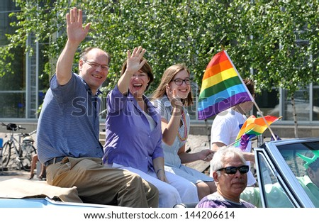 MINNEAPOLIS - JUNE 30:  US Senator Amy Kloubuchar,  with her husband and daughter, wave to the crowd at the Twin Cities Gay Pride Parade on June 30, 2013, in Minneapolis. - stock photo