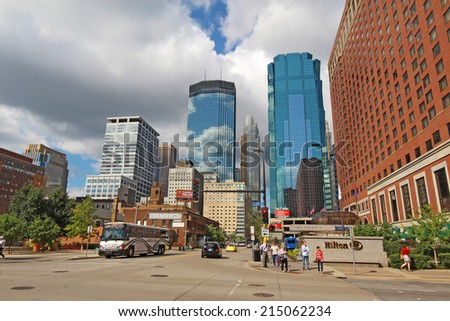 MINNEAPOLIS, MINNESOTA - AUGUST 11 2014: Pedestrian and car traffic moves through downtown Minneapolis, the seat of Hennepin County and the largest city in Minnesota with over 400,000 residents. - stock photo