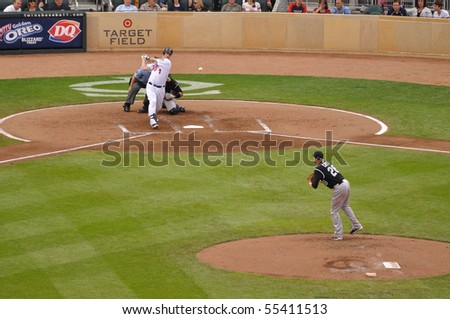 MINNEAPOLIS, MN - JUNE 15: 2009 AL MVP Joe Mauer of the Minnesota Twins hits a pitch from Colorado Rockies pitcher Aaron Cook on June 15, 2010 in Minneapolis, MN - stock photo