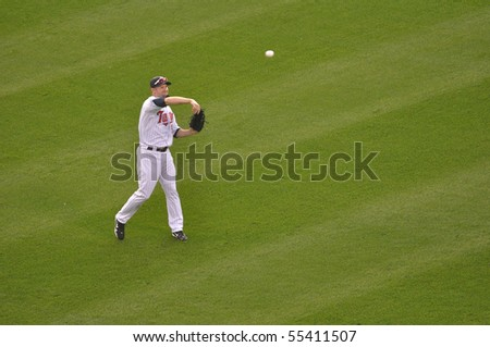 MINNEAPOLIS, MN - JUNE 15: Michael Cuddyer of the Minnesota Twins tosses a baseball during a game against the Colorado Rockies on June 15, 2010 in Minneapolis, MN - stock photo