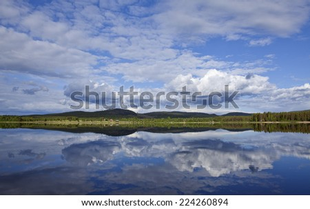 Minor buildings, farm along the river. Meadows, hills, rock and a gently river this side. Reflections in the water.  - stock photo
