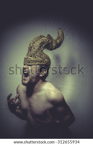 Minotaur, naked man with helmet warrior trumpets, and pain nightmare - stock photo