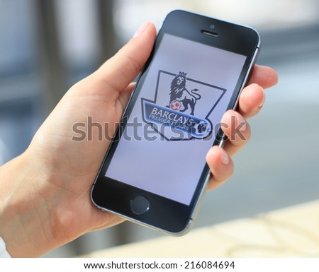 MINSK, BELARUS - AUGUST 17, 2014: Woman holding brand new black Apple iPhone 5S. The official logo of the England national football championship. Premier League. - stock photo