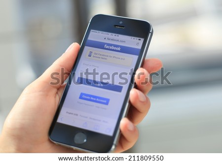 MINSK, BELARUS - AUGUST 17, 2014: Woman holding brand new black Apple iPhone 5S with loging in Facebook app. Facebook the largest social network in the world.  - stock photo