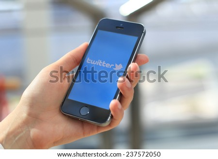 MINSK, BELARUS - AUGUST 16, 2014: Woman holding brand new white Apple iPhone 5S. Twitter is an online social networking and microblogging. - stock photo