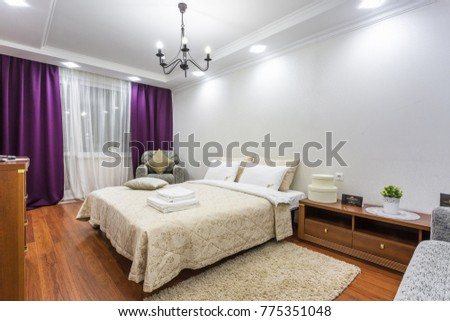 MINSK, BELARUS - DECEMBER 8, 2017: Interior of the modern bedroom in flat in light color style with violet curtains