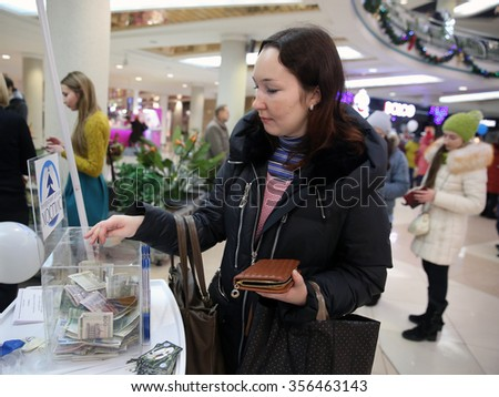 MINSK, BELARUS - DECEMBER 29, 2015: Woman donates money for the new building of Belarusian Children's Hospice
