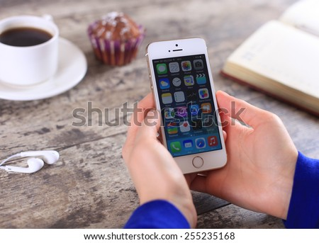 MINSK, BELARUS - February 22, 2015: Woman holding brand new white Apple iPhone 5S. Social media are trending and both business as consumer are using it for information sharing and networking.  - stock photo