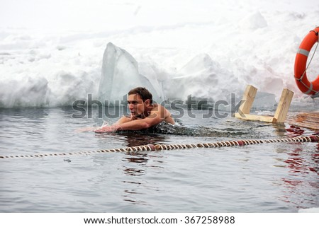 MINSK, BELARUS - JANUARY 19, 2016: Amateur swimmers compete in freezing lake water commemorating Epiphany. Air temperature is 10F (-12C)