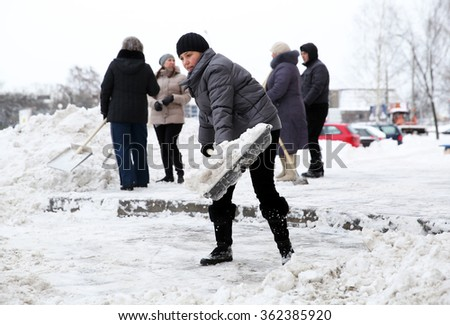 MINSK, BELARUS - JANUARY 14, 2016: Female shovels away snow