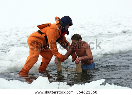 MINSK, BELARUS - JANUARY 19, 2016: lifeguard helping a young man after bathing in open lake water commemorating the baptism of Jesus. Air temperature is 10°F (-12°C).