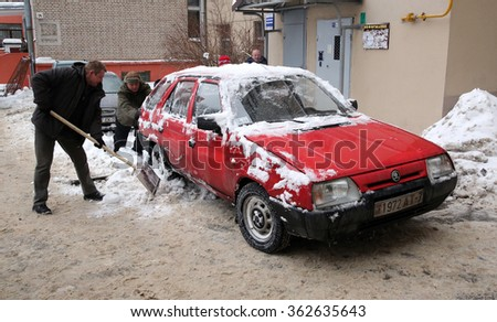 MINSK, BELARUS - JANUARY 15, 2016: People help a car driver to move from the snow banks