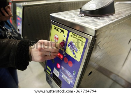 MINSK, BELARUS - JANUARY 26, 2016: Subway passenger's hand drops a token to the turnstile