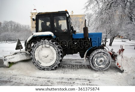 MINSK, BELARUS - JANUARY 12, 2016: Tractor removes snow from pavement. The Daniella Cyclone has brought a lot of snow to Belarus