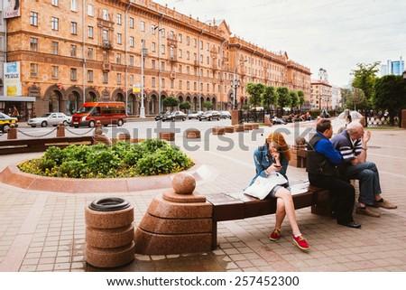 MINSK, BELARUS - June 3, 2014: People resting, sitting on bench on Lenin Street in summer - stock photo