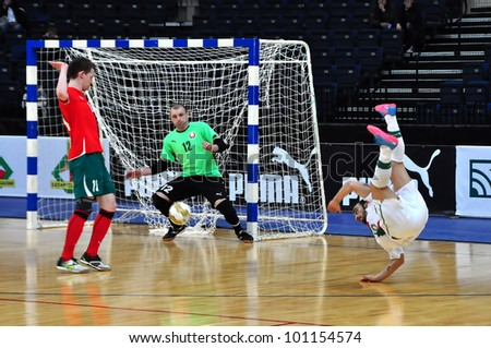 MINSK, BELARUS - MARCH 26: qualification World Cup 2012, Belarus � Portugal: Pavel Shvayba (goalkeeper(BLR) , Vladimir Zhdanovich(BLR) and Ricardinho (kicking) on March 26, 2012 in Minsk, Belarus - stock photo