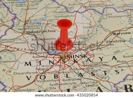 Minsk Belarus marked on map with red pushpin. Selective focus on the word Minsk and the pushpin. Pin is in an angle.  - stock photo