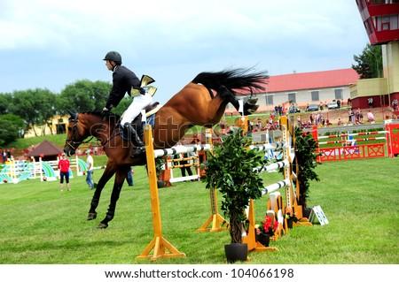 MINSK, BELARUS - MAY 27: Benas GUTKAUSKAS (LTU) and his horse CARNAVAL SILLA jump over the barrier during KAP JUMPING HORSE SHOW 2012 on May 27, 2012 in Minsk, Belarus. - stock photo