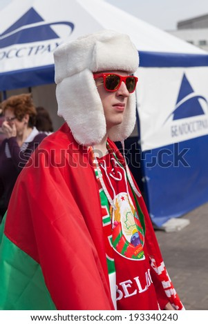 "MINSK, BELARUS - May 17, 2014: ICE HOCKEY WORLD CHAMPIONSHIP, MINSK-ARENA, The hockey fan from Belarus in white hat ""ushanka"" with national flag in the uniform of national team of Belarus - stock photo"