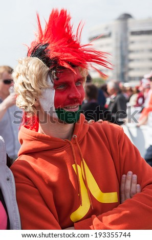 MINSK, BELARUS - May 17, 2014: ICE HOCKEY WORLD CHAMPIONSHIP, MINSK-ARENA, The hockey fan from Belarus with national flag on the fac�e in bright colored wig - stock photo