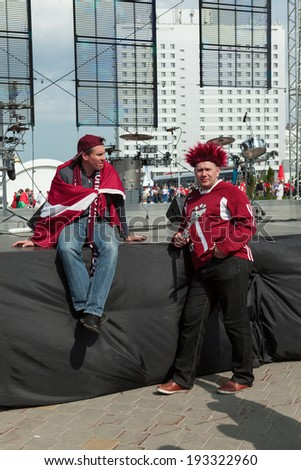 MINSK, BELARUS - May 17, 2014: ICE HOCKEY WORLD CHAMPIONSHIP, MINSK-ARENA, The hockey fans from Latvia with national flags in uniform upset after defeating Russian - stock photo