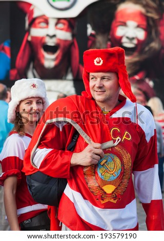 "MINSK, BELARUS - May 18, 2014: ICE HOCKEY WORLD CHAMPIONSHIP, MINSK-ARENA, The hockey fans from Russia with national flag in the uniform of a national team and hats ""ushanka"" - stock photo"