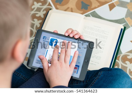Minsk, Belarus - November 25, 2016: Boy teenager sitting on the floor and registered in the social network Facebook on iPad Apple.
