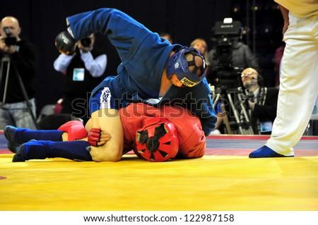 MINSK, BELARUS - NOVEMBER 10: Ivanov A. from Russia (blue) VS Velichkov B. from Bulgary during the final match SAMBO (Wrestling) WORLDCh-2012 on November 10, 2012 in Minsk, Belarus. - stock photo