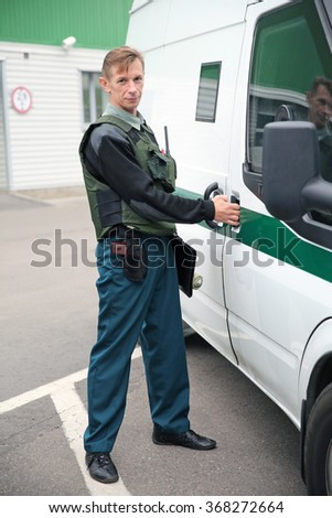 MINSK, BELARUS - OCTOBER 05, 2015: Cash-in-transit (CIT) guard armed with a handgun enters the CIT van