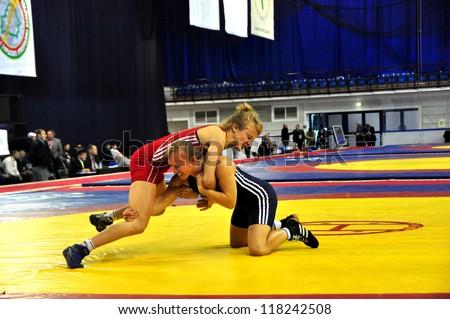 MINSK, BELARUS - SEPTEMBER 16: Unidentified female (red) goes for the score during Grand Prix for the prizes A.Medved in freestyle wrestling on September 16, 2012 in Minsk, Belarus. - stock photo