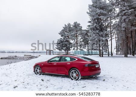 Minsk region / Belarus - 14 November 2016: Tesla Model S with red in a snow-covered forest near the water