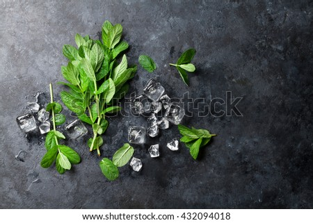 Mint and ice on stone table. Top view with copy space - stock photo